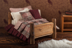 Tiny wooden bed with bedding and pouf