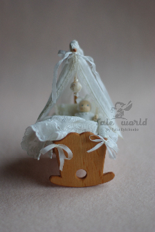 Miniature wooden baby cradle with unique bedding and baldachin